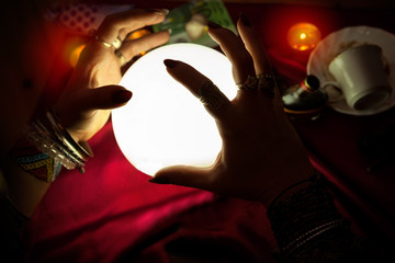 Hands of fortune teller woman above illuminated crystal ball