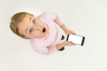 The surprised girl stand with a smartphone. View from above