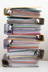 Seven folders with documents stacked in pile on the table