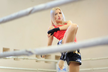 Muay Thai girl. World WMF Amateur Champion Muay Thai. Fighting on sport box ring. Young adult woman kickboxing training exercise on the sport box ring  with black boxing wraps