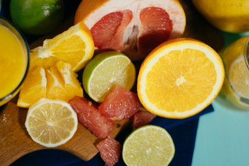 Citrus, oranges, lemons, limes, grapefruit, pomelo on vintage board, lemonade and juice in a glass of glass on a turquoise background