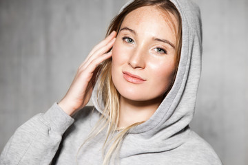Portrait of young naturally beautiful woman in a gray sweatshirt on the cement wall background