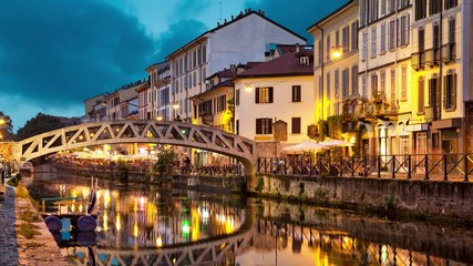 Fototapete - Bridge across the Naviglio Grande canal at the evening in Milan, Italy (static image with animated sky and water)