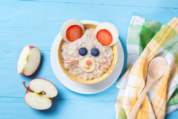 Funny oat porridge with mouse face made of fruits and berries, food for kids idea, top view