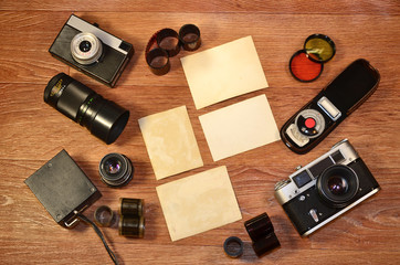 Top View of Vintage photo camera and other old retro photography accessories on wooden table plate with some clear white blank photo frames to placed your pictures or text