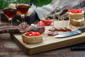 Bread, sausage, red wine, glass, cutting board and knife arranged on a wooden table for a snack in the countryside.