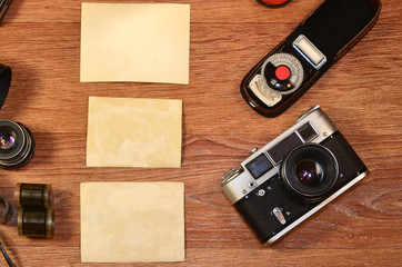 Vintage camera, photography accessories and blank photo frames on wooden table. Still life with copy space. Top view. Retro toned image in beige colors