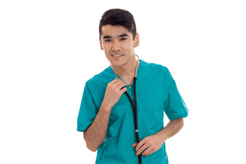 a young doctor in the blue dress with stethoscope smiles and looks into a camera