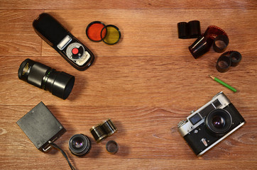 Top View of Vintage photo camera and other old retro photography accessories on wooden table