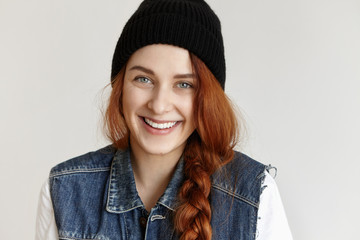 Close-up portrait of beautiful young redhead European woman with braid smiling happily, showing her perfect white teeth while posing indoors, dressed in sleeveless jeans jacket and stylish black hat