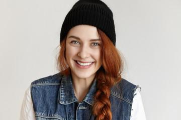 Headshot of pretty girl in stylish clothing, smiling joyfully enjoying happy teenage life. Fashionable young redhead female wearing hipster black hat and sleeveless denim jacket posing indoors
