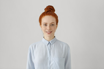 Indoor shot of attractive young redhead female with hair bun in shirt smiling happily, ready for her first day at new work. Cute student girl with freckles getting dressed before going to college