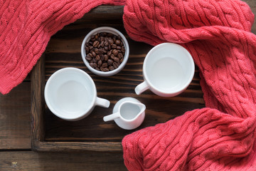 Two white cup, cream and coffee beans in box. Dark wooden background. Pink woven scarf. Beautiful vintage coffee groundwork. Coloring and processing photo.