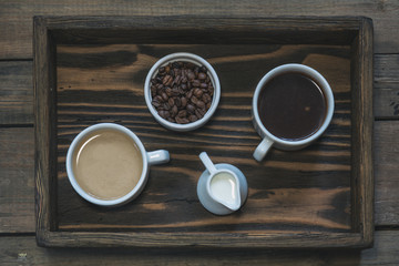 Cup of black coffee, cup of coffee with milk, cream and coffee beans in box. Dark wooden background. Beautiful vintage coffee groundwork. Coloring and processing photo.