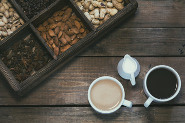 Cup of black coffee, cup of coffee with milk, cream. Almond, pistachios, anise, peanut and coffee beans in box. Dark wooden background. Beautiful vintage coffee groundwork. Coloring photo.