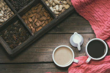 Cup of black coffee, cup of coffee with milk, cream.  Pink woven scarf. Almond, pistachios, anise, peanut and coffee beans in box. Dark wooden background. Coloring and processing photo.