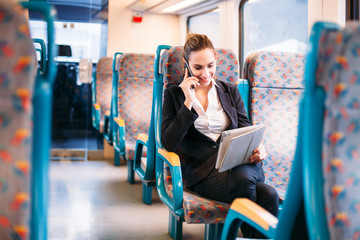 Young millennial businesswoman traveling train bus talking phone