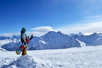 snowboarder standing with snowboard in the mountains.
