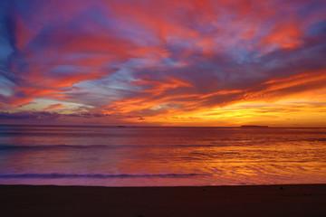 Fiery pink orange and yellow beach sunset
