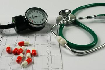Stethoscope and cardiogram on white background.