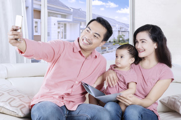 Smiling family taking selfie picture at home
