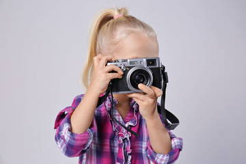 Cute girl with film camera on light background