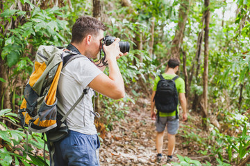 nature photographer in tropical jungle, group of tourists hiking in the forest, man taking photo with big camera