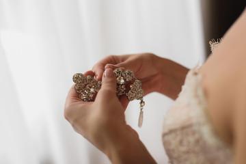 Bride is holding earrings
