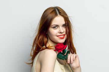 happy woman with a red rose on a light background