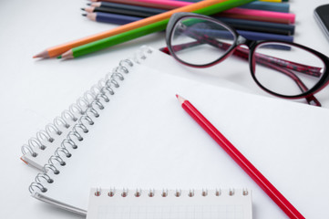 Red pencil on a white notepad and a number of glasses and pencils