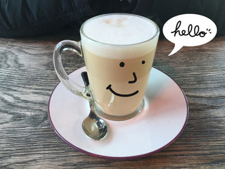 Cute white coffee cup smile and say hello on wooden table