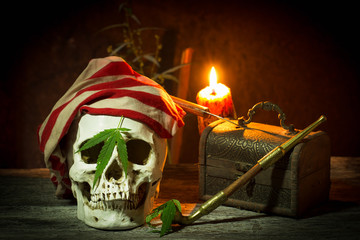 Pirate comedian skull with cannabis, marijuana in black still life style