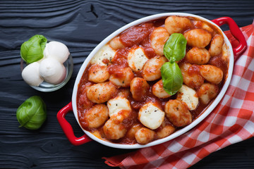 Casserole with potato gnocchi alla Sorrentina on a black wooden background, above view