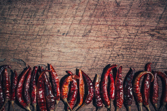 Dried red chilli pepper on wood background. Top view