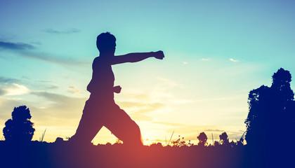 man training karate on sunset.