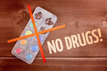 Open multicolored pills on a wooden background with inscription No drugs and prohibition sign