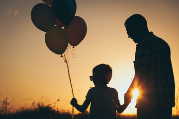 Father and son playing with balloons in the park at the sunset time.