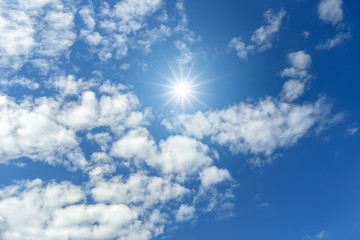 Blue sky with clouds and sun reflection. looking up view