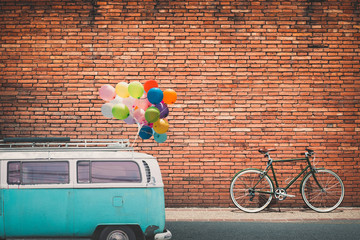 Wall Mural - Classic car (vintage van) in city with colorful balloon on roof parked on road in urban. concept of love in summer and wedding, honeymoon. flim grain filter effect