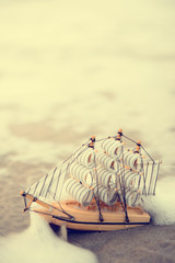Sailing ship model on the beach, discovery concept in vintage tone style