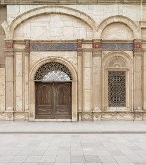 Decorated Window and wooden ornate door over white marble decorated wall. One of the entrances of the Mosque of Muhammad Ali Pasha (Alabaster Mosque), Citadel of Cairo, Egypt