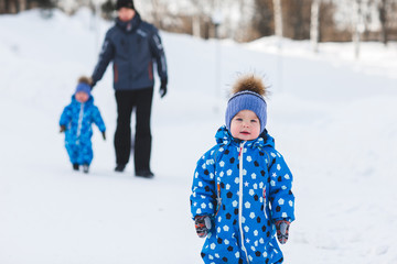 Portrait of cute boy twin in winter Park on background of his father and brother