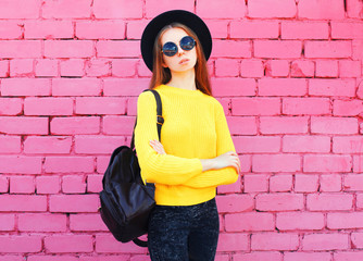 Fashion portrait woman wearing a black hat and yellow knitted sweater over colorful pink bricks background