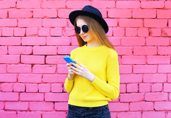 Fashion pretty cool girl using smartphone over colorful pink brick background