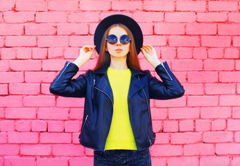 Fashion woman wearing a black hat and yellow knitted sweate rjacket over colorful pink bricks background