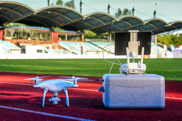Drone is ready for take off. White quadcopter with four motors and propellers standing in large stadium next to its carry box and remote controller with touchpad, waiting for work. Aerial footage