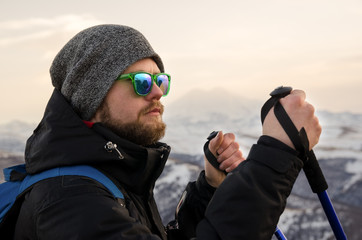 Young bearded hipster wearing a hat and sunglasses with Nordic walking sticks and a backpack moves in the mountains at sunset, against a background of sunset sky and volcano Elbrus
