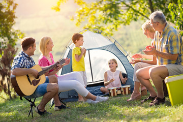 family playing a guitar and singing.
