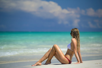 Beautiful young woman with blond hair is sitting on the beach