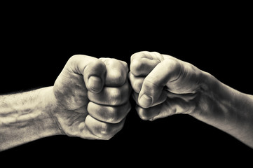 black and white image close up clash of two fists on black background. Concept of confrontation, competition etc.